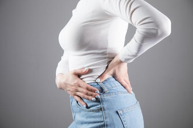 若い女性が灰色のシーンで腎臓を痛める