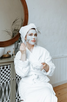 Молодая женщина в халате с полотенцем на голове надевает маску в ванную.