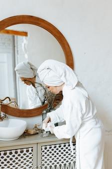 Молодая женщина в халате с полотенцем, обмотанным вокруг головы, расстилает органическую маску для лица в миске в ванной комнате.