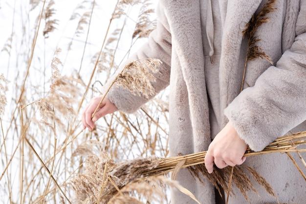 Молодая женщина в бежевом платье нейтральных цветов собирает пампасную траву
