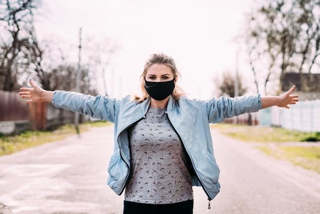Молодая женщина в черной медицинской маске в бирюзовом пиджаке и серой футболке