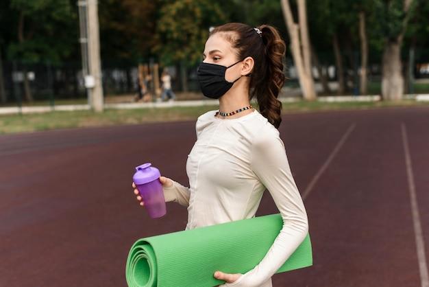 黒い保護マスクを着用した若い女性が、ボトル入り飲料水を持って運動場に立っています。