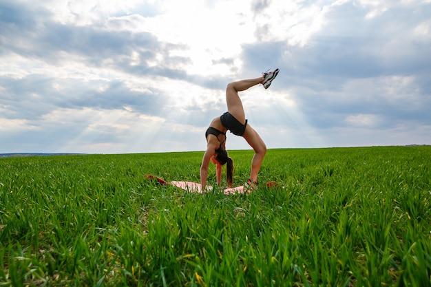 Молодая женщина в черном топе и шортах выполняет стойку на руках. модель стоит на руках, делает гимнастический шпагат на фоне голубого неба. концепция здорового образа жизни