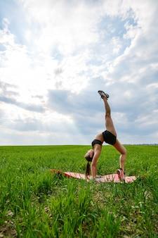 黒のトップスとショートパンツの若い女性が逆立ちをします。モデルが彼女の手に立って、青い空を背景に体操の分割を行っています。健康的なライフスタイルのコンセプト