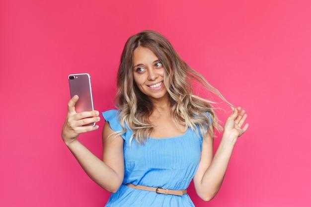 青いドレスを着た若い女性は、明るい色のピンクの背景に彼女の携帯電話で自分撮りをします