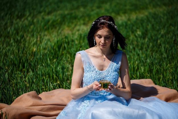 青い長いドレスを着た若い女性は、棺を手に緑の野原に座っています。彼女の顔に笑顔で美しい少女のファッションの肖像画。婚約指輪ボックス