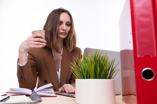 茶色のビジネススーツを着た若い女性が職場でコーヒーを飲みます。孤立
