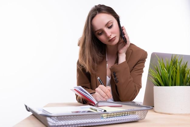 電話で話し、机のノートに書いている茶色のビジネススーツの若い女性