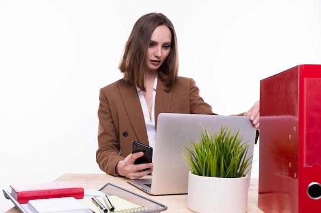 白い背景の上のラップトップで働いているビジネススーツの若い女性。孤立
