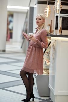 휴대 전화와 그녀의 손에 커피 종이 컵을 들고 쇼핑 센터에있는 카페에서 젊은 여자.