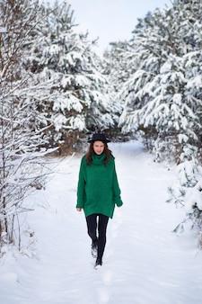 짙은 녹색 스웨터와 모자에 젊은 여자가 아름다운 겨울 숲 한가운데 서