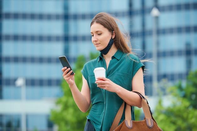 수축 의료 얼굴 마스크에 젊은 여자는 스마트 폰에서 뉴스를 읽고 시내에서 커피를 마시는