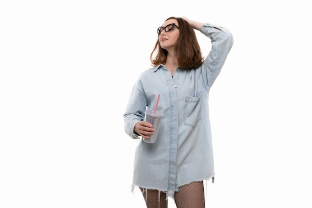 Молодая женщина в джинсовой рубашке и колготках пьет коктейль из стакана