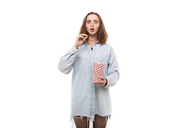 デニムシャツを着た若い女性がポップコーンを食べる