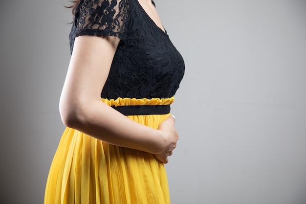 드레스를 입은 젊은 여성이 복통이 있습니다.