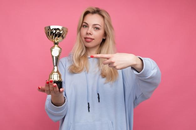 Молодая женщина в модной толстовке с капюшоном держит золотой кубок