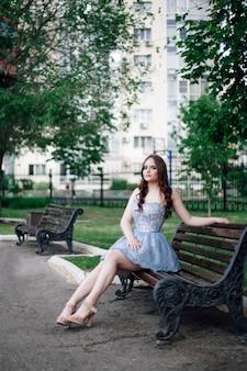 Девушка в праздничном коротком синем корсетном платье изящно сидит на деревянной скамейке в городском парке ...