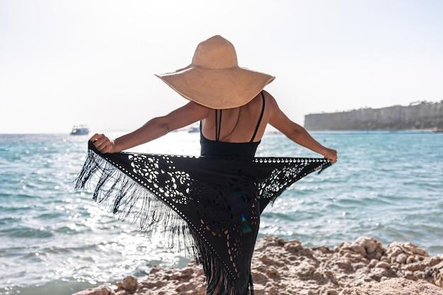 모자와 망토를 입은 젊은 여성이 바다 근처에서 쉬고 있습니다.