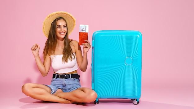 帽子のデニムのショートパンツと白いトップの若い女性は、彼女の手に書類とパスポートを保持します