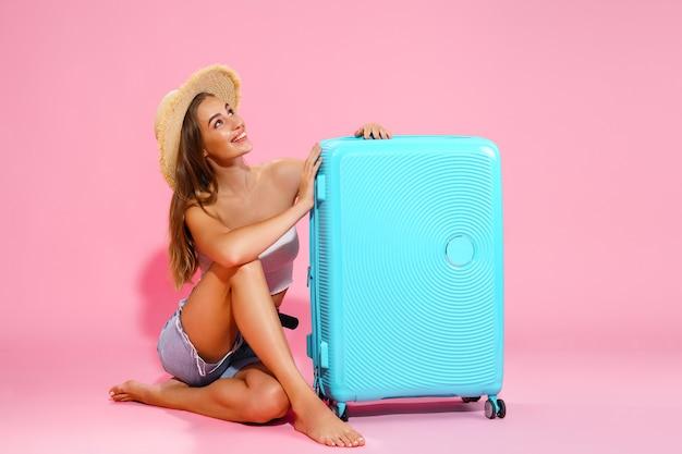 青いスーツケースの近くに座っている間、帽子のデニムのショートパンツと白いトップスの若い女性が見上げる