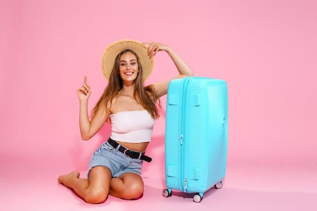 従業員を指している青いスーツケースの近くに座っている間、帽子のデニムのショートパンツと白いトップの若い女性...