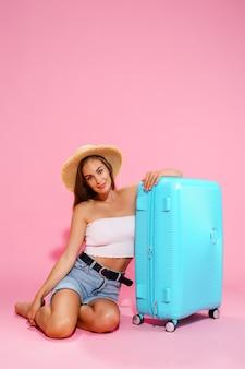青いスーツケースの近くに座っている間、帽子のデニムのショートパンツと白いトップの若い女性
