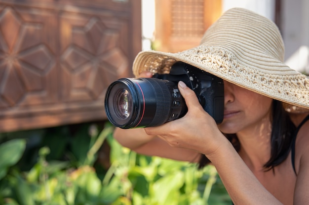 모자를 쓴 젊은 여성이 더운 여름날 전문 slr 카메라로 사진을 찍습니다.