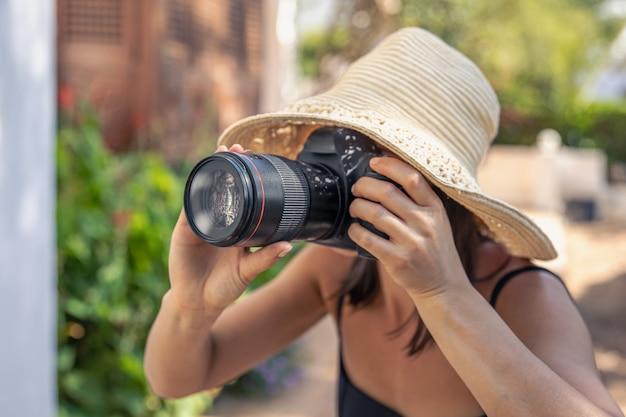 Молодая женщина в шляпе делает снимки на профессиональную зеркальную камеру в жаркий летний день.