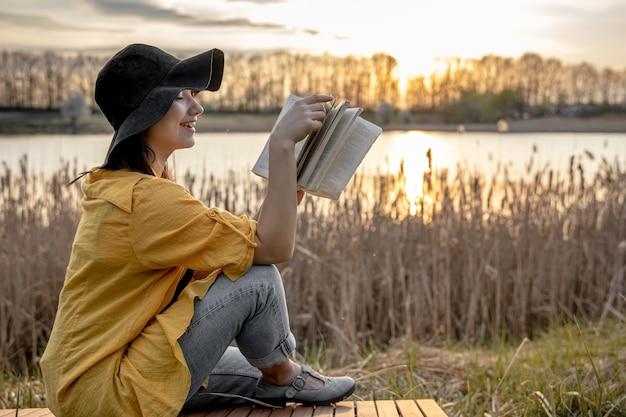 그녀의 얼굴에 미소를 가진 모자에있는 젊은 여자가 석양 강가에 앉아 책을 읽고 있습니다.