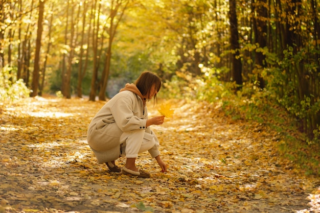 긴 셔츠를 입은 젊은 여성이 가을 숲의 아름다운 자연 경관에서 나뭇잎을 모은다
