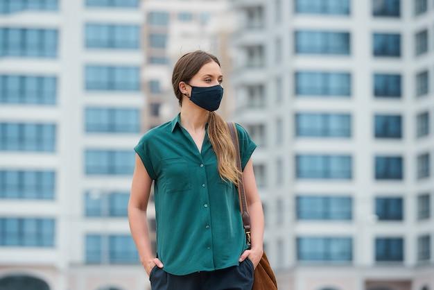 의료 얼굴 마스크에 젊은 여자가 걷고있는 동안 바지 주머니에 손을 밀고있다