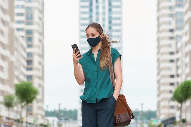 의료 얼굴 마스크에 젊은 여자는 바지의 주머니에 손을 밀어 그녀의 스마트 폰 뉴스를 읽고 고층 빌딩 사이 산책