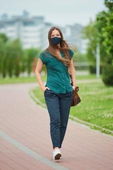의료 얼굴 마스크에서 젊은 여자는 공원에서 바지 주머니에 밀어 넣는 손을 걷고