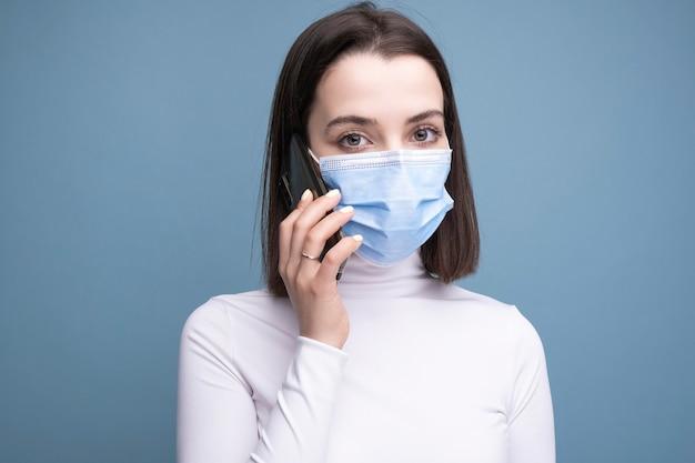 의료용 마스크를 쓴 한 젊은 여성이 손에 휴대전화를 들고 스튜디오의 파란색 배경에서 셀카를 만듭니다.