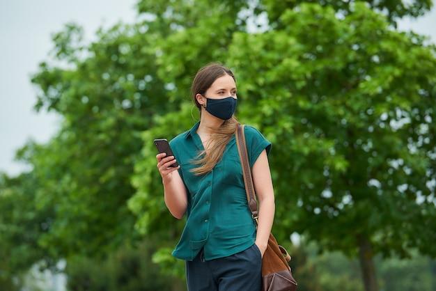 네이비 블루 의료 얼굴 마스크의 젊은 여성이 걷는 바지 주머니에 손을 밀어 넣는 스마트 폰 뉴스를 읽습니다.