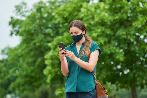 네이비 블루 의료 얼굴 마스크에 젊은 여자는 공원에서 산책하는 동안 스마트 폰에서 뉴스를 읽습니다