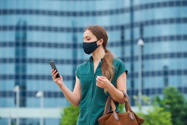 도시의 중심에 코로나 바이러스의 확산을 피하기 위해 감색 의료 얼굴 마스크에 젊은 여자