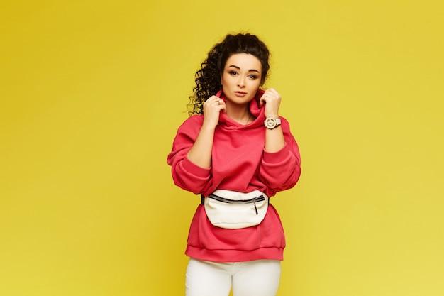 ピンクのパーカーと白いズボンの若い女性が黄色の壁で隔離されました。黄色の壁の上の都市のスポーツウェアでアフロの髪型を持つモデルの女の子