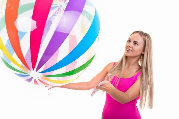 Молодая женщина в розовом купальнике держит цветной надувной мяч