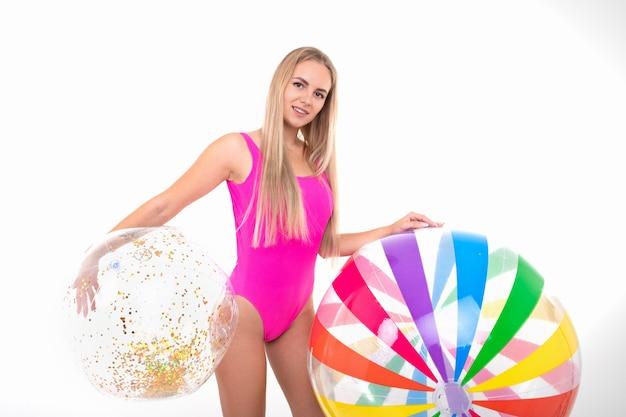 Молодая женщина в розовом купальнике держит цветные надувные мячи
