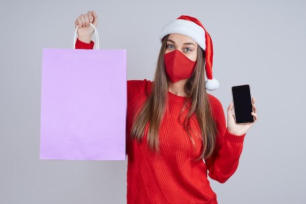 Молодая женщина в защитной маске, в шляпе санты, держит бумажный пакет
