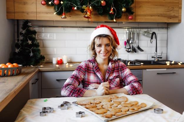 赤いチェックのシャツと赤い帽子をかぶった若い女性が、クリスマスのお祝いのためにキッチンでジンジャークッキーを準備します。