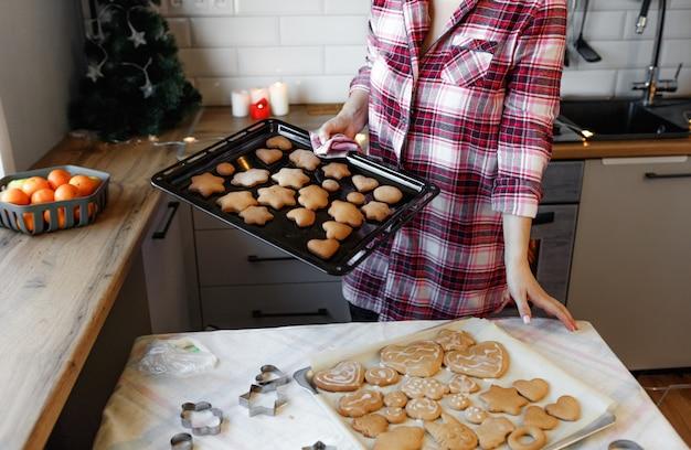 Молодая женщина в красной клетчатой рубашке готовит имбирное печенье на кухне к празднованию рождества.