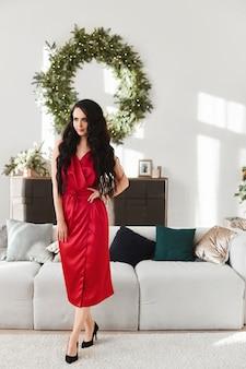 Молодая женщина в красном вечернем платье над интерьером гостиной, украшенной к рождеству