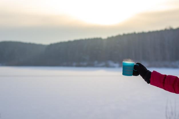 겨울에 빨간 재킷을 입은 젊은 여성이 뜨거운 커피나 차 한 잔을 들고 있습니다. 눈 덮인 겨울과 당신을 따뜻하게 해줄 따뜻한 음료. 뜨거운 커피 또는 차 한잔