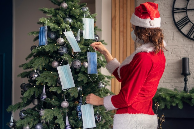 빨간 산타클로스 의상을 입은 젊은 여성이 의료용 마스크로 크리스마스 트리를 장식합니다. 격리 휴가. 코로나바이러스 제한에 따라 새해와 크리스마스를 축하하는 개념.