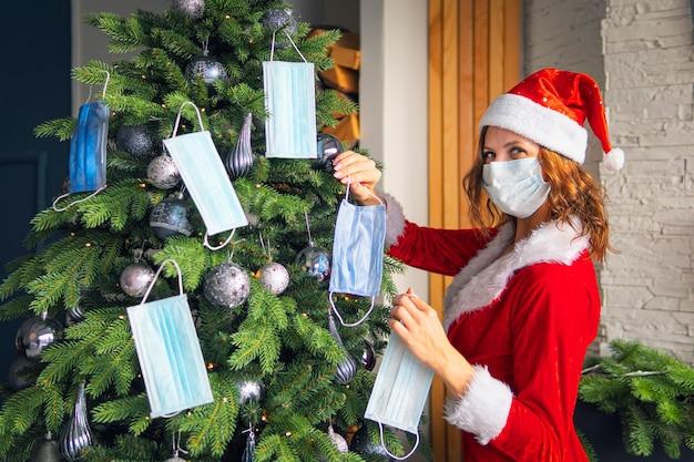 빨간 산타클로스 의상을 입은 젊은 여성이 의료용 마스크로 크리스마스 트리를 장식합니다. 코로나바이러스 제한 하에서 새해와 크리스마스를 축하하는 개념. 격리 휴가