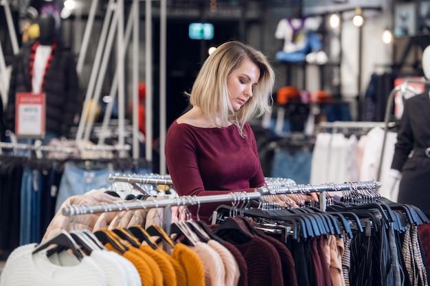 Молодая женщина в торговом центре, покупая одежду