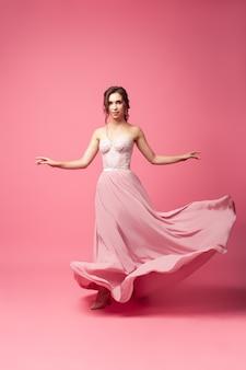 ピンクの孤立した背景にシルクのドレスを着た若い女性は、長いイブニングドレスのモデルの女性です...