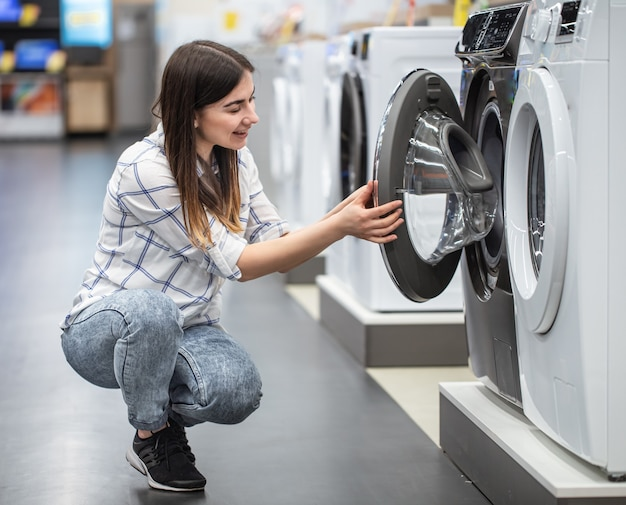 店の若い女性が洗濯機を選ぶ..ショッピングのコンセプト。